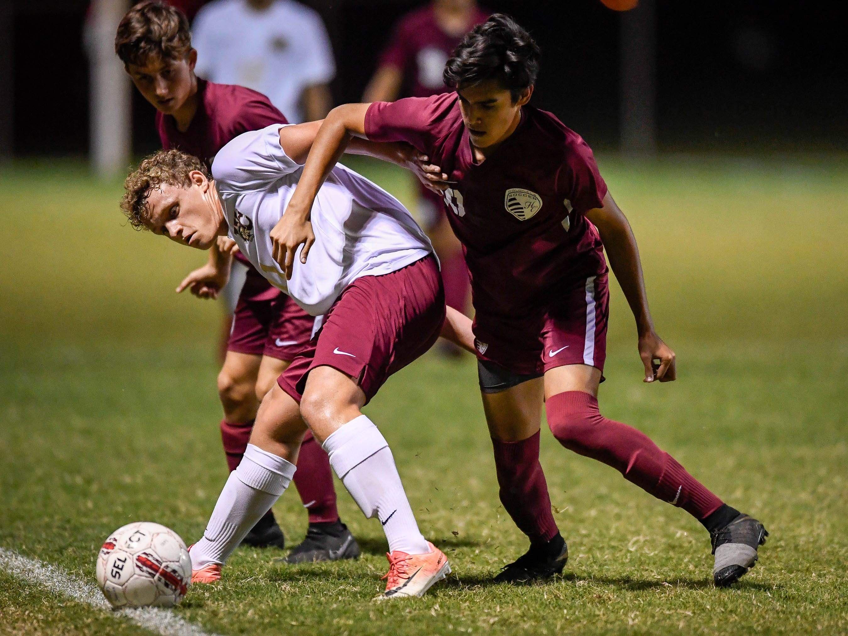 Webster's Joel McCormick (11)  and Henderson County's David Gonzalez (10) battle on the side line as the Henderson County Colonels play the Webster County Trojans in the Sixth District Soccer Tournament at Colonel Field Wednesday, October 10, 2018.