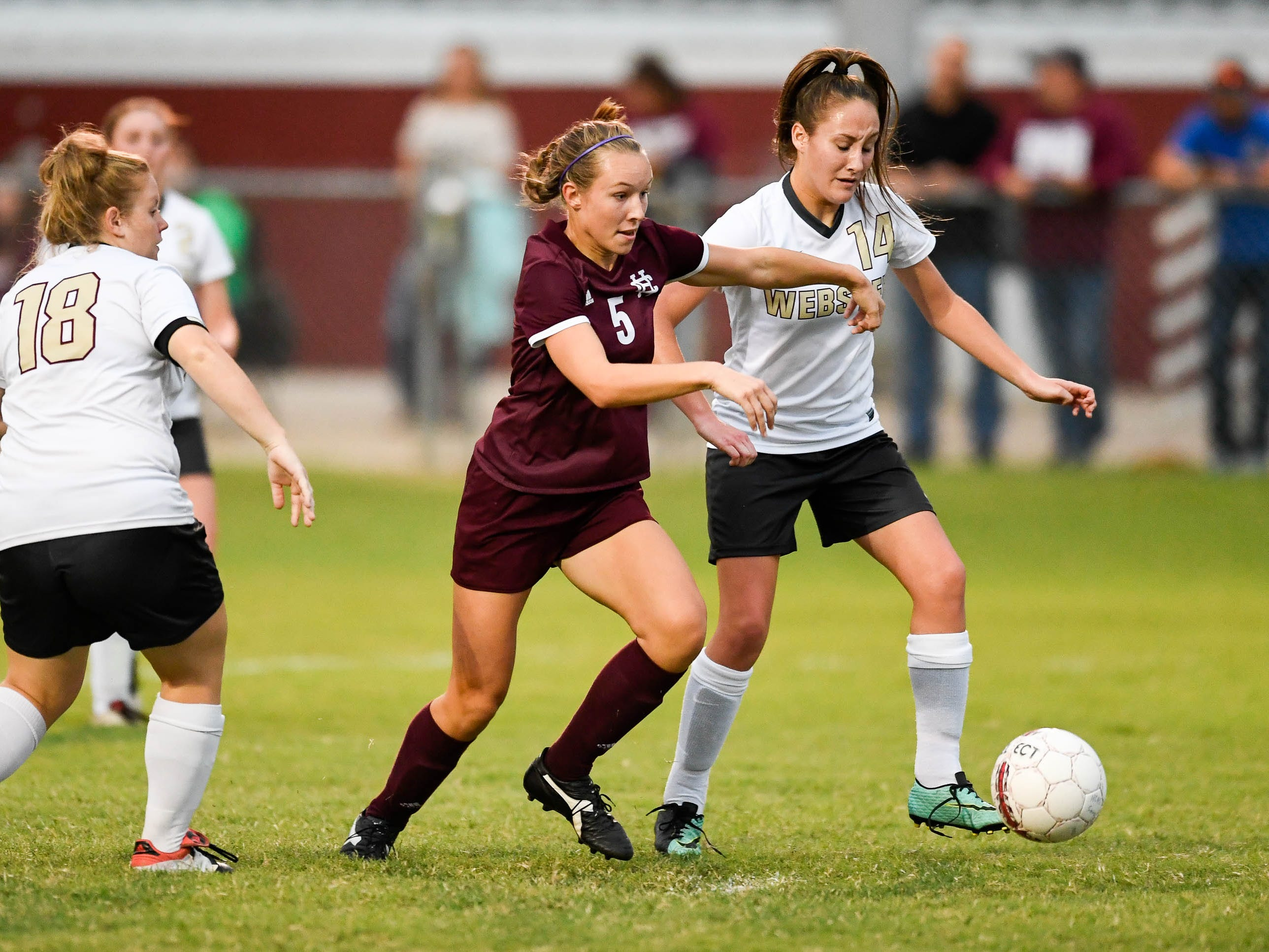 Henderson's Maddie Griggs (5) drives past Webster's Brooklyn Conrad (14) to score a goal as the Henderson County Lady Colonels play the Webster County Lady Trojans in the Sixth District Soccer Tournament at Colonel Field Wednesdayt, October 10, 2018.
