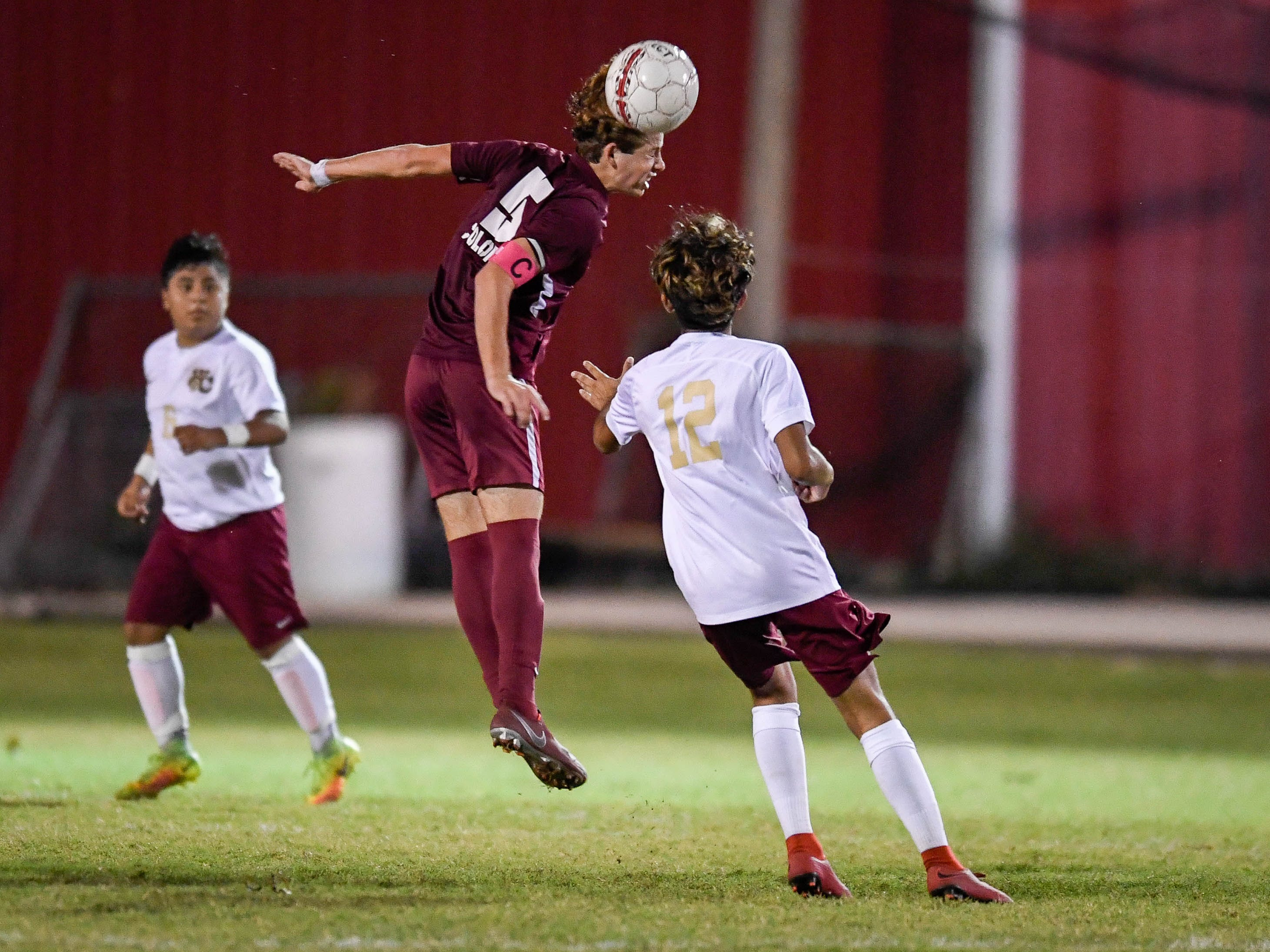 Henderson County's Cale Wright (5) heads the ball over defense from Webster's Erick Escalante (12) as the Henderson County Colonels play the Webster County Trojans in the Sixth District Soccer Tournament at Colonel Field Wednesday, October 10, 2018.