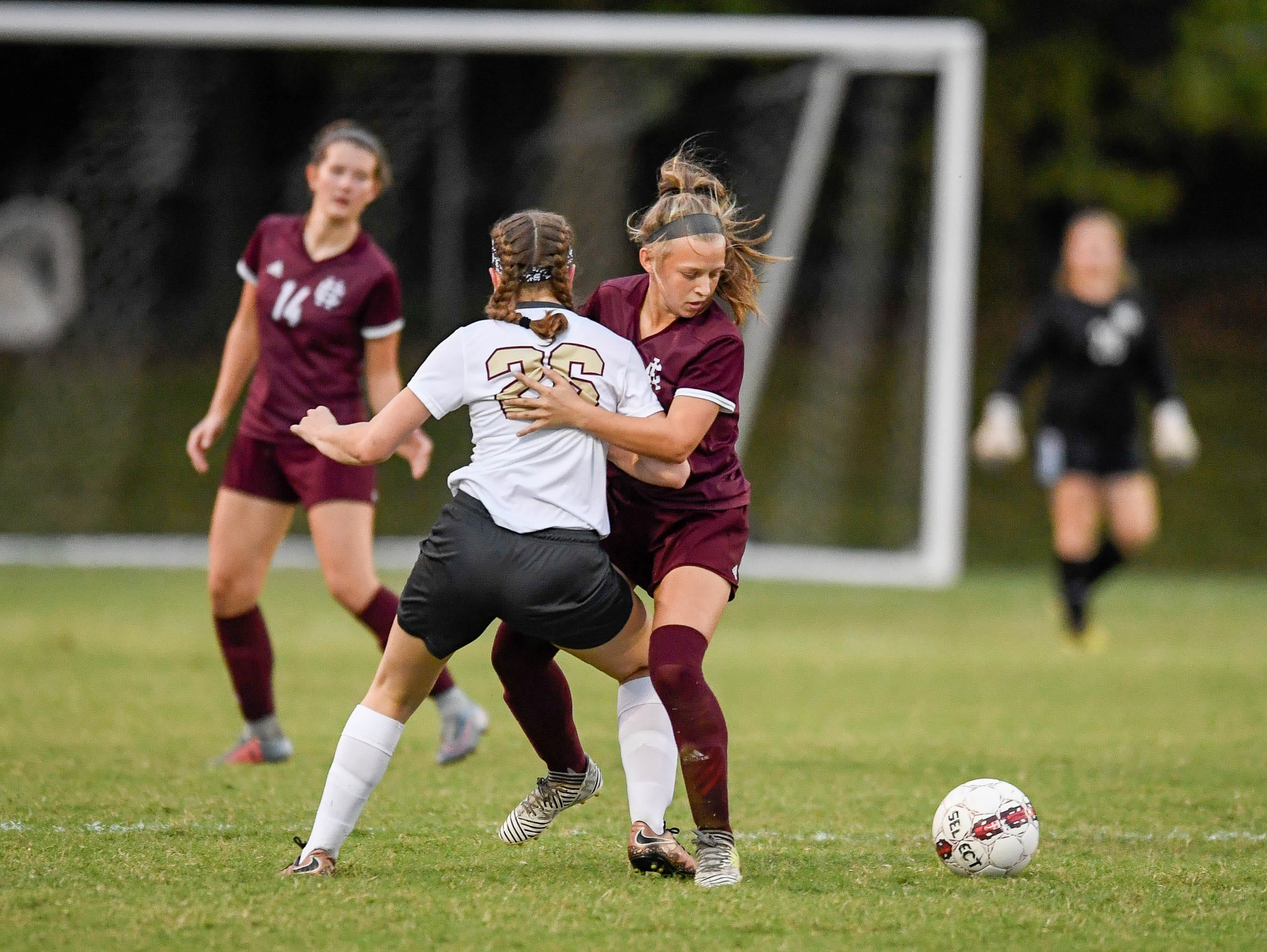 Webster's Marissa Austin (26)  and Henderson's Morgan Greene (20) battle for control of the ball as the Henderson County Lady Colonels play the Webster County Lady Trojans in the Sixth District Soccer Tournament at Colonel Field Wednesdayt, October 10, 2018.