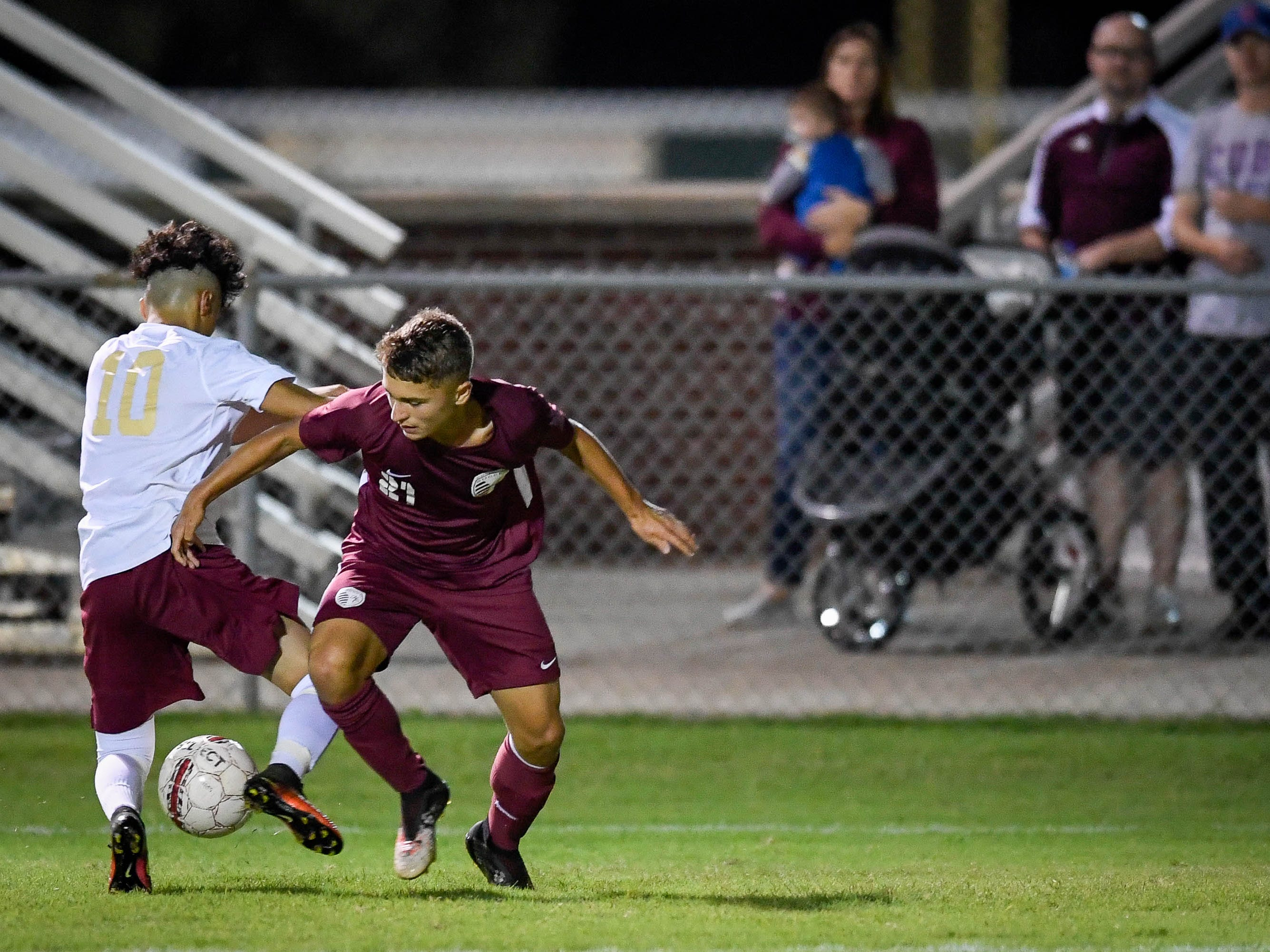 Webster's Santos Portillo (10) and Henderson County's Ashton Todd (21) battle as the Henderson County Colonels play the Webster County Trojans in the Sixth District Soccer Tournament at Colonel Field Wednesday, October 10, 2018.