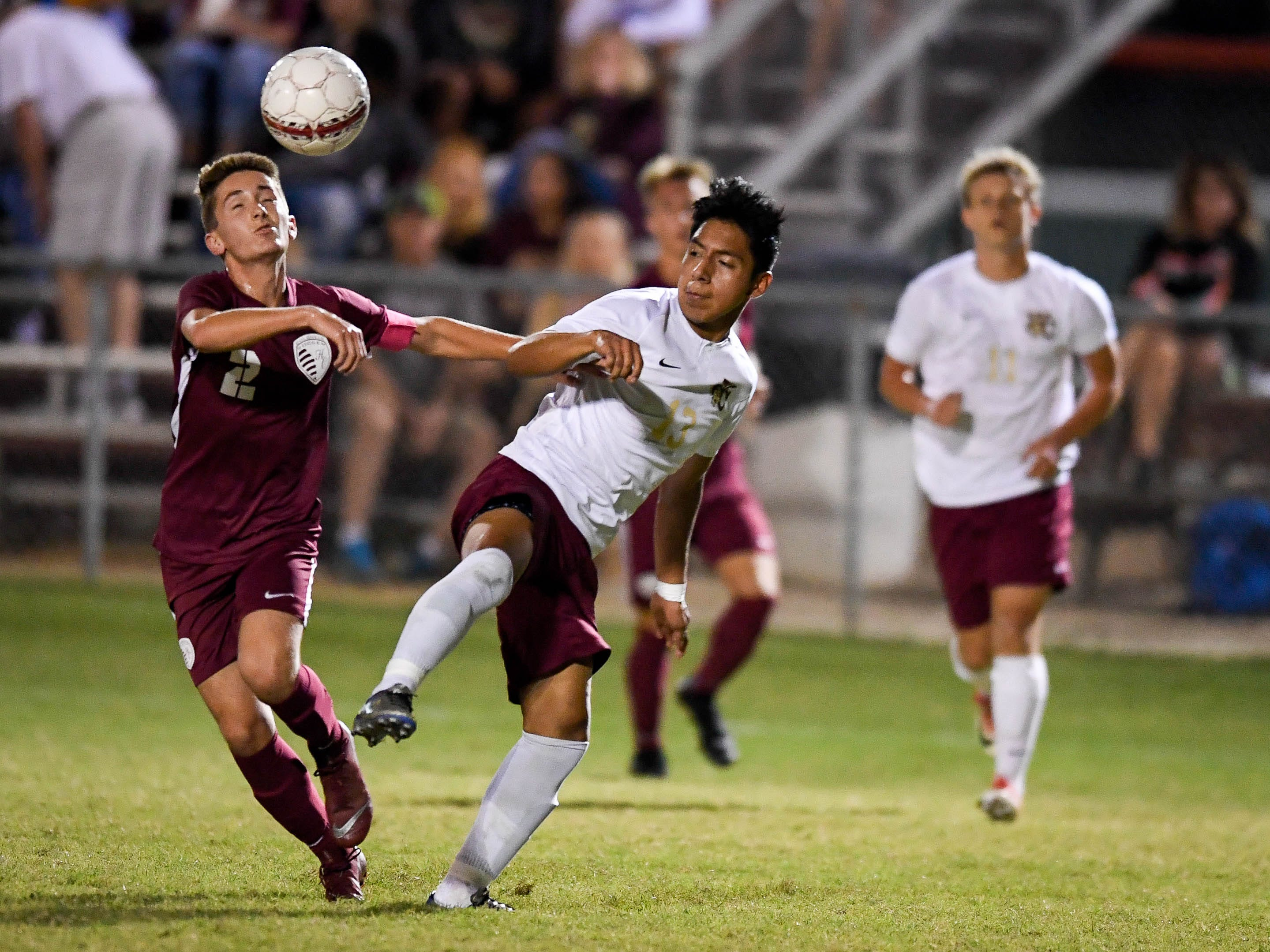 Henderson County's Samuel Cloutier (2) and Webster's Michael Velazquez (13) try to control the ball as the Henderson County Colonels play the Webster County Trojans in the Sixth District Soccer Tournament at Colonel Field Wednesday, October 10, 2018.