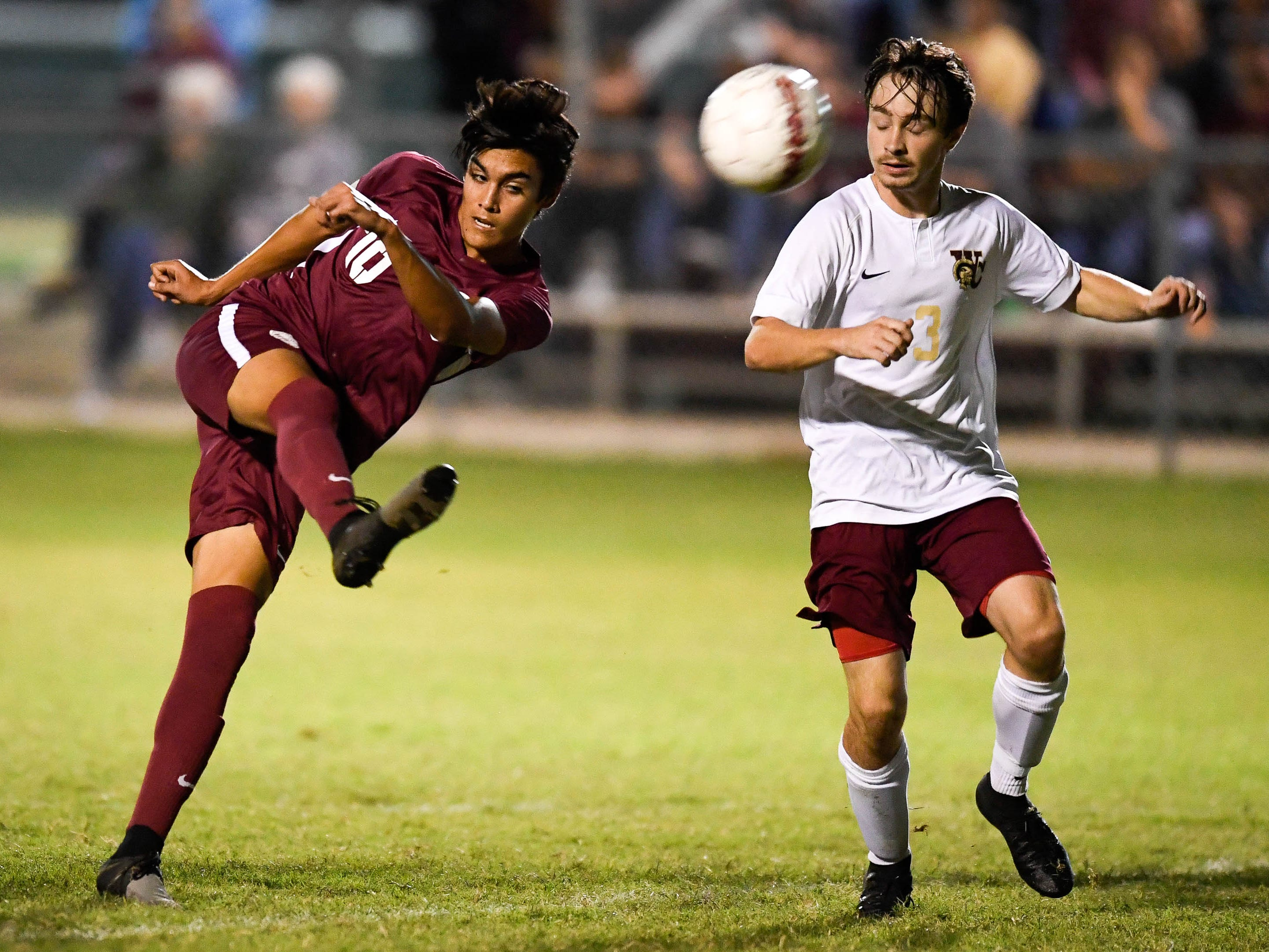 Henderson County's David Gonzalez (10) with a goal kick under defensive pressure from Webster's Drake Newcom (3) as the Henderson County Colonels play the Webster County Trojans in the Sixth District Soccer Tournament at Colonel Field Wednesday, October 10, 2018.