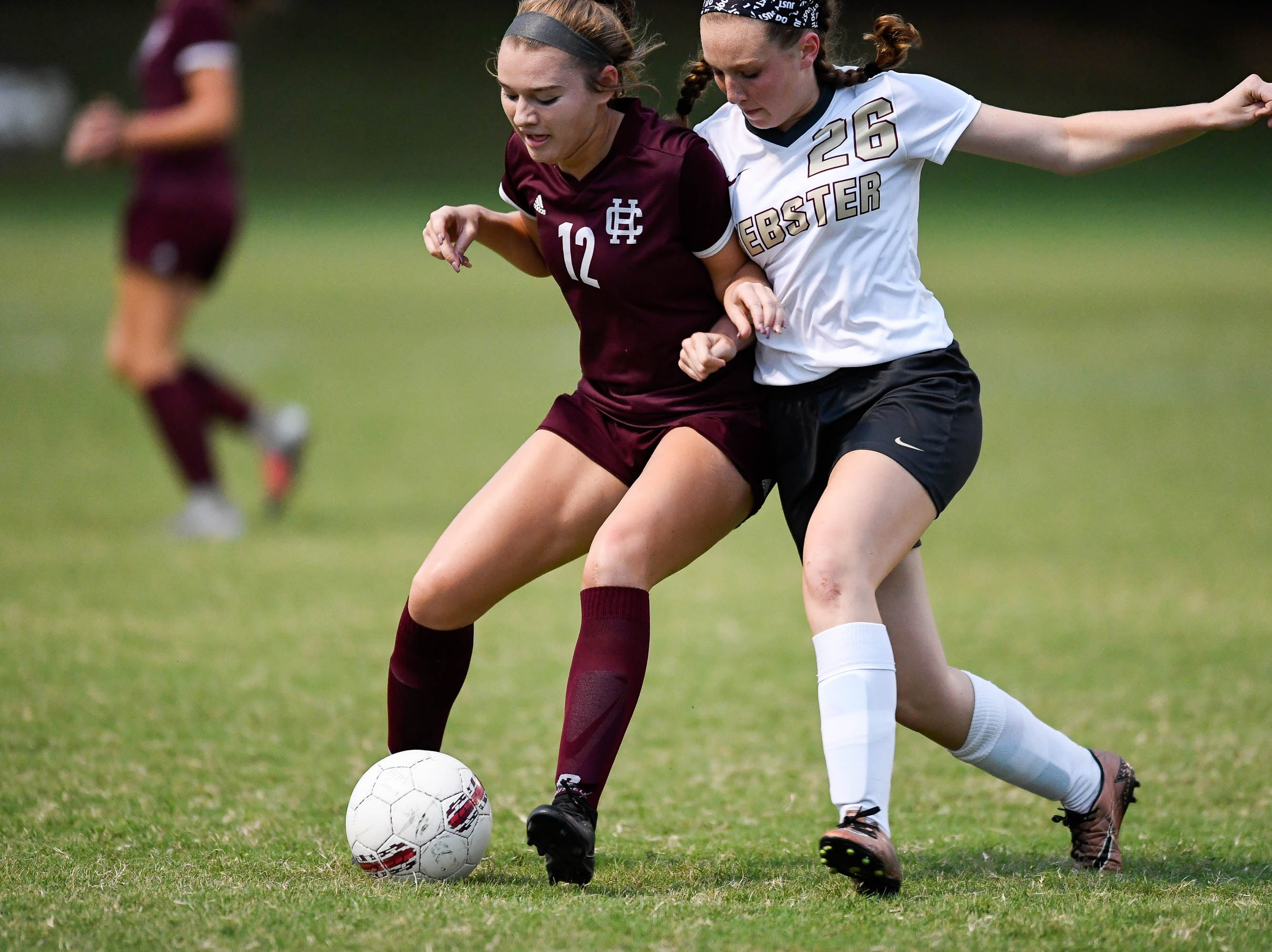 Henderson's Whitnie West (12) and Webster's Marissa Austin (26) battle for the ball as the Henderson County Lady Colonels play the Webster County Lady Trojans in the Sixth District Soccer Tournament at Colonel Field Wednesdayt, October 10, 2018.