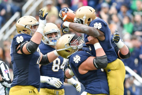 Fighting Irish running back Dexter Williams (2) celebrates with offensive lineman Sam Mustipher (53) after a touchdown in the Blue-Gold Game at Notre Dame Stadium.