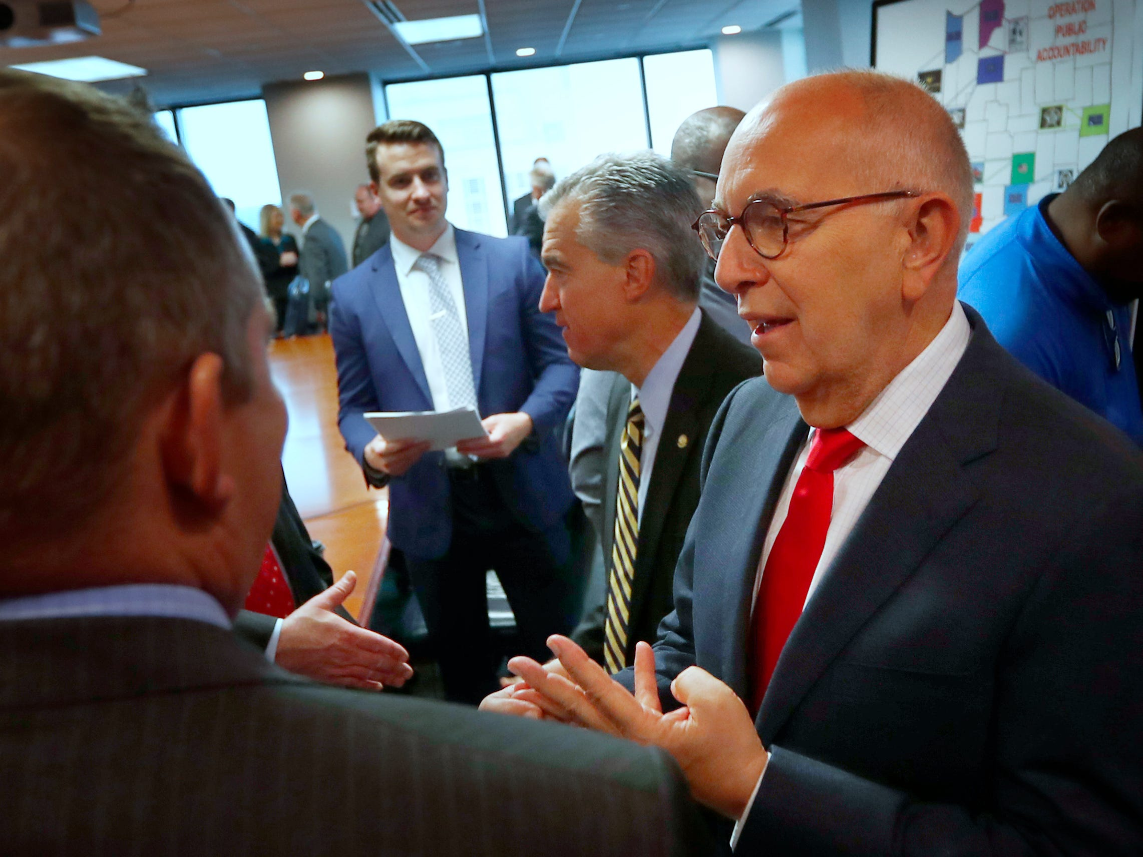 "U.S. Attorney for the Southern District of Indiana Josh Minkler, center, and Marion County Prosecutor Terry Curry, right, speak to people after a press conference at the U.S. Attorney's office, Thursday, Oct. 11, 2018.  U.S. Attorney Minkler, the FBI, Indiana State Police, and the State Board of Accounts release details about joint operation in a crackdown involving ""state-wide corruption,"" from Operation Public Accountability."