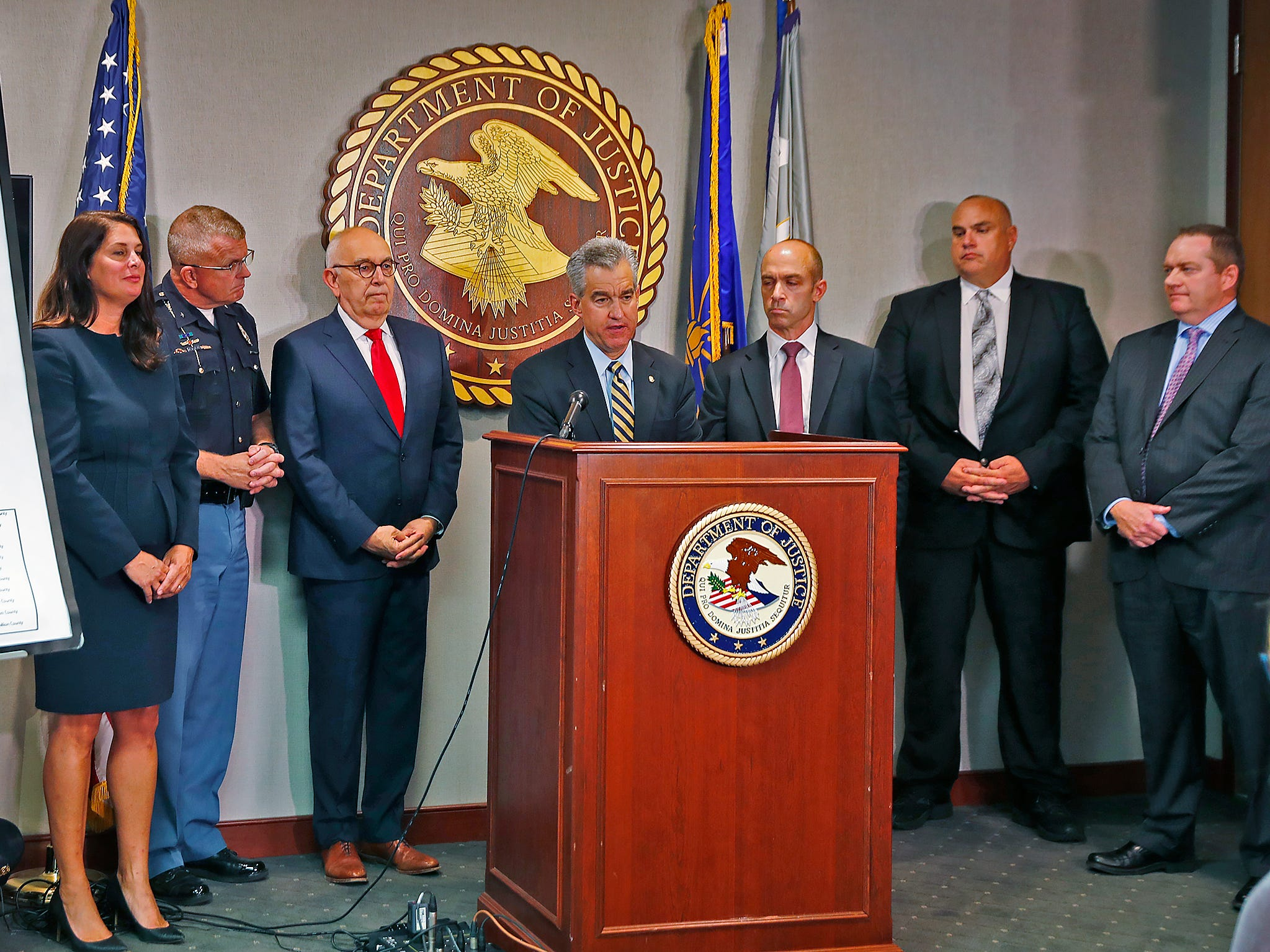 "U.S. Attorney for the Southern District of Indiana Josh Minkler, center, speaks during a press conference at the U.S. Attorney's office, Thursday, Oct. 11, 2018.  U.S. Attorney Minkler, the FBI, Indiana State Police, and the State Board of Accounts release details about joint operation in a crackdown involving ""state-wide corruption,"" from Operation Public Accountability. From left to right: Assistant U.S. Attorney Tiffany Preston, Indiana State Police Superintendent Doug Carter, Marion County Prosecutor Terry Curry, Minkler, FBI Special Agent in Charge Grant Mendenhall, Indiana State Board of Accounts State Examiner Paul Joyce, and Deputy Executive Director of the Indiana Prosecuting Attorney's Council Chris Naylor."
