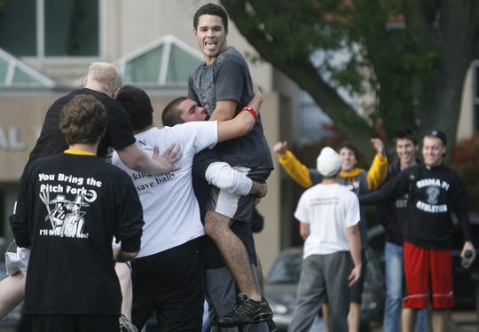 In this Oct. 6, 2009 file photo, UI sophomore Cody Gordon, of Des Moines, is hoisted in the air by freshman Joe Brodt, of Elmhurst, Ill., after their dodgeball team from Sigma Nu beat the team from the Sigma Pi fraternity as part of the Homecoming Week festivities, at Hubbard Park, in Iowa City, Iowa.