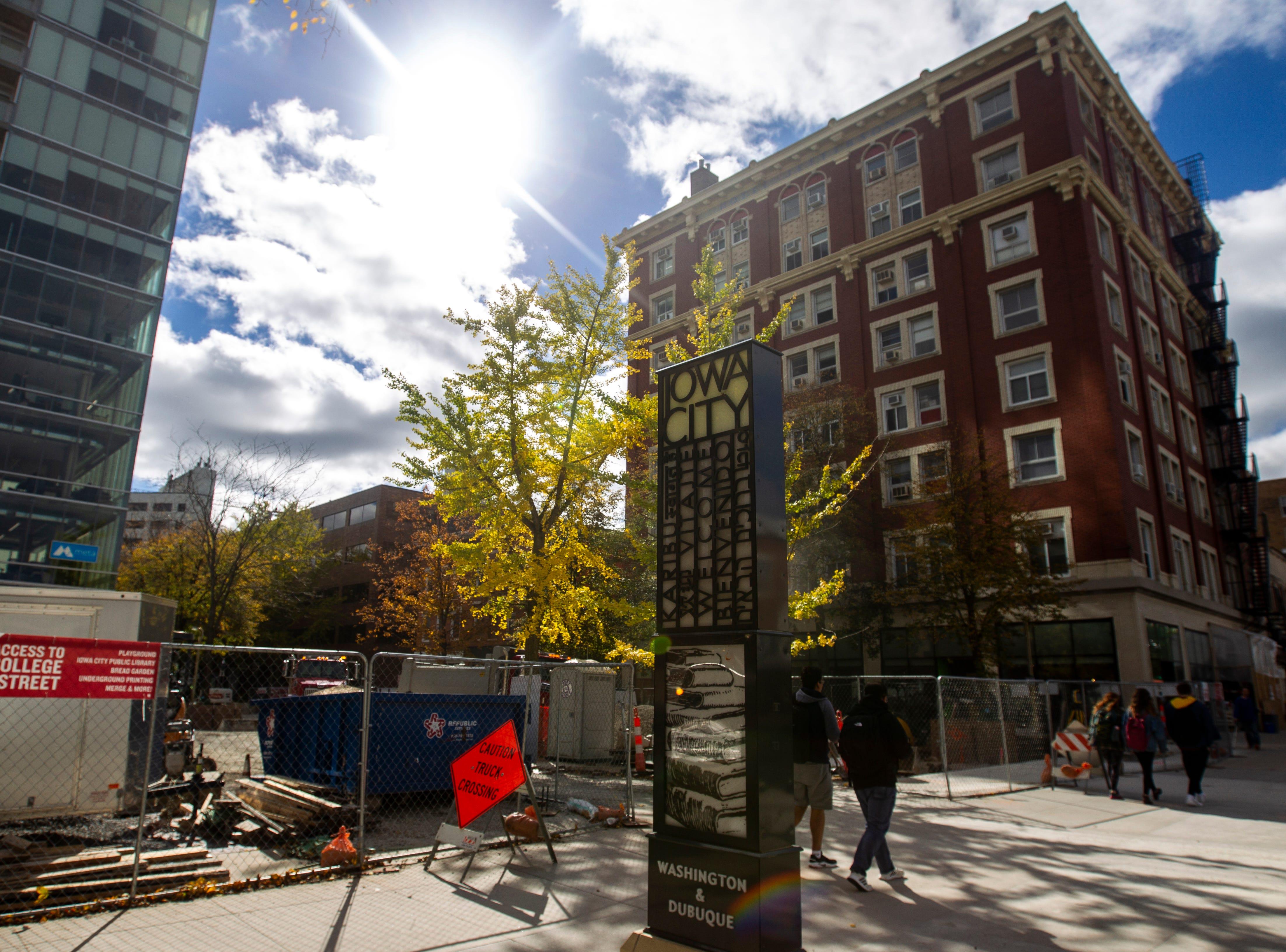 People walk along Washington Street towards the Jefferson Building while construction continues on updates to the pedestrian mall on Thursday afternoon, Oct. 11, 2018, in downtown Iowa City.