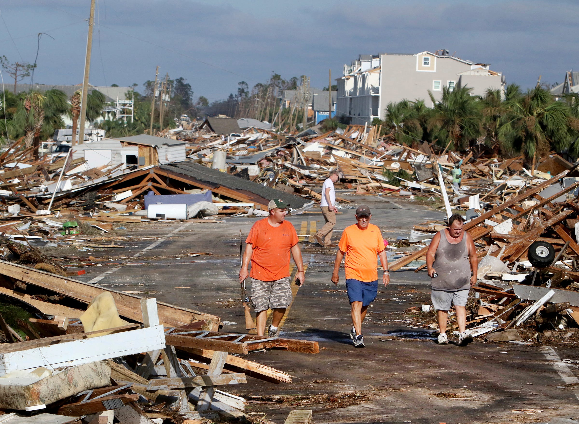 From left: Lee Cathey, 37, Al Cathey, 71, and Charles Smith, 56, survey damage in the coastal township of Mexico Beach, Fla., population 1200, which lay devastated on Thursday, Oct 11, 2018, after Hurricane Michael made landfall on Wednesday in the Florida Panhandle. Brock said he stayed in the city to ride out the storm.