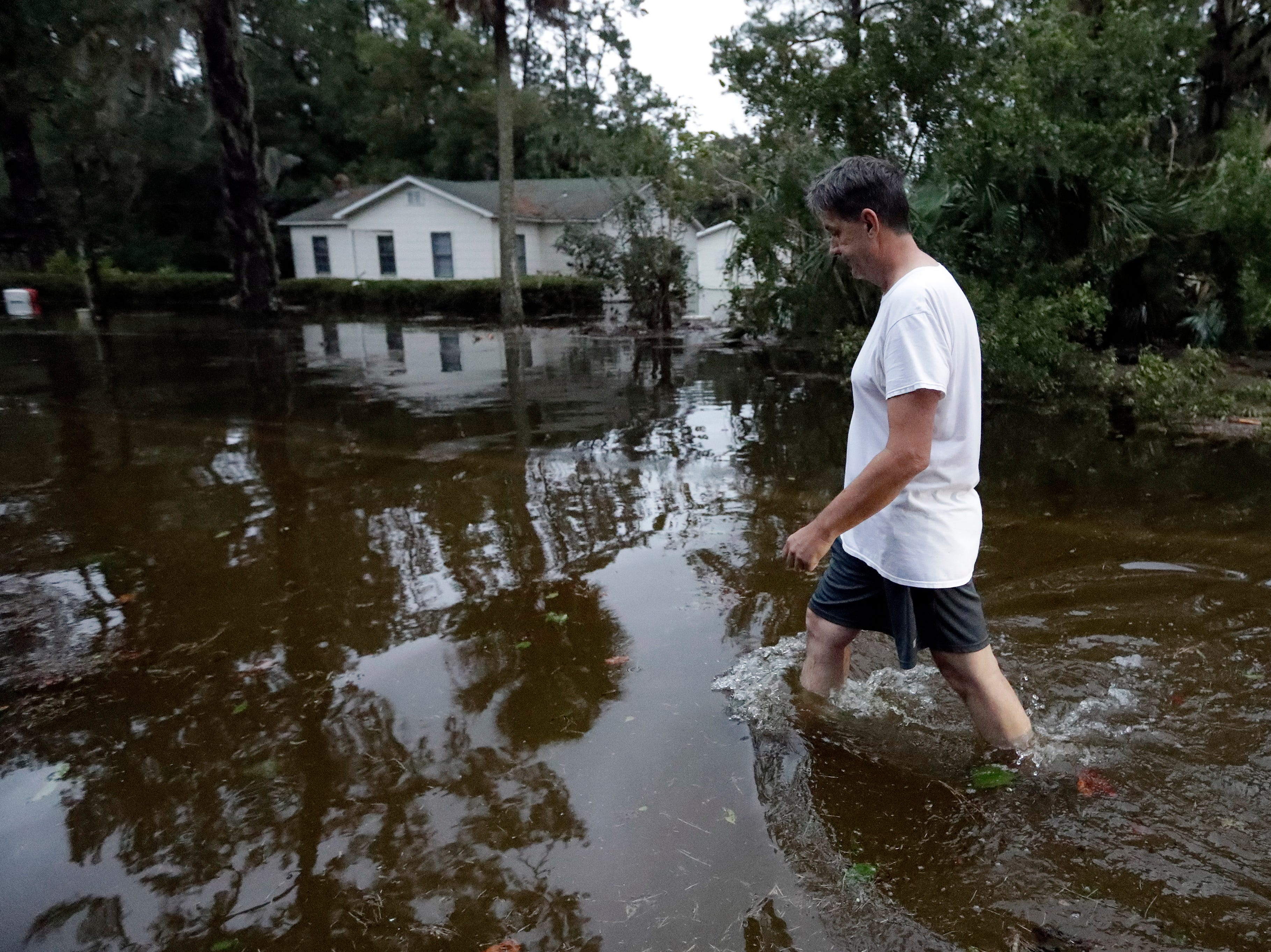 John Gouge walks through flood waters as he goes to check on the post office Wednesday, Oct. 10, 2018, in St. Marks, Fla. Supercharged by abnormally warm waters in the Gulf of Mexico, Hurricane Michael slammed into the Florida Panhandle with terrifying winds of 155 mph Wednesday, splintering homes and submerging neighborhoods before continuing its march inland.