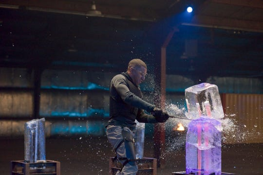 "A contestant on ""Forged in Fire: Knife or Death"" slices through a block of ice while taking on the show's obstacle course."