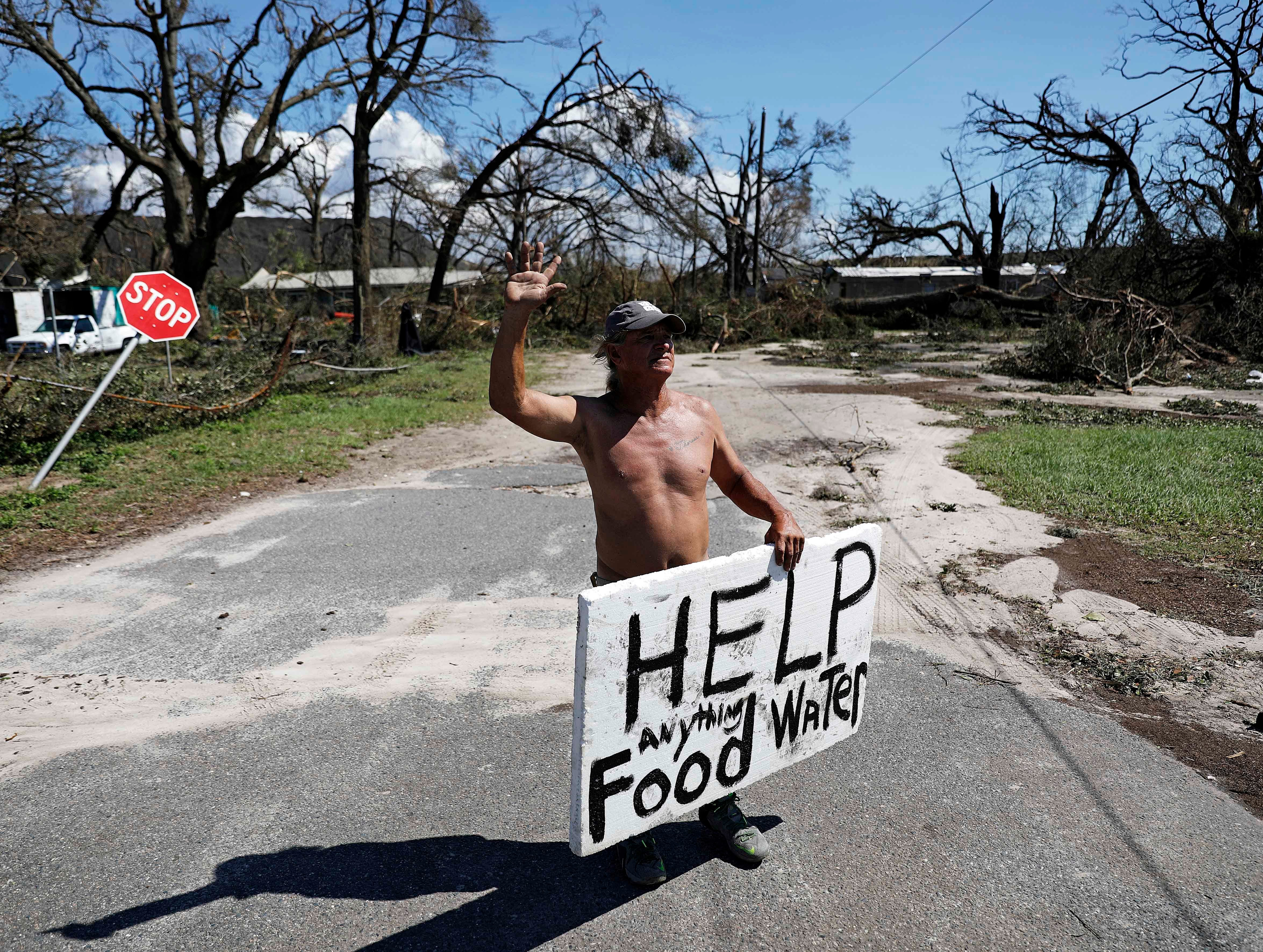 """Michael Williams, 70, waves to passing motorists while looking for food and water as downed trees prevent him from driving out of his damaged home with his family in the aftermath of Hurricane Michael in Springfield, Fla., Thursday, Oct. 11, 2018. """"I don't know what I'm going to,"""" said Williams."""