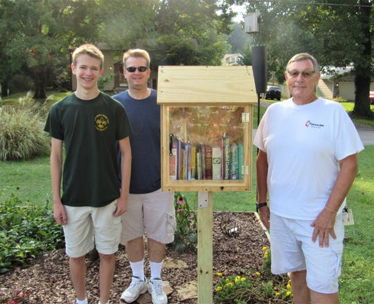 Michael Davis, left, stands beside his first library box in Concord United Methodist Church's Butterfly Garden.  Proud dad Scott Davis and CUMC's Mike Smith fully supported the project.