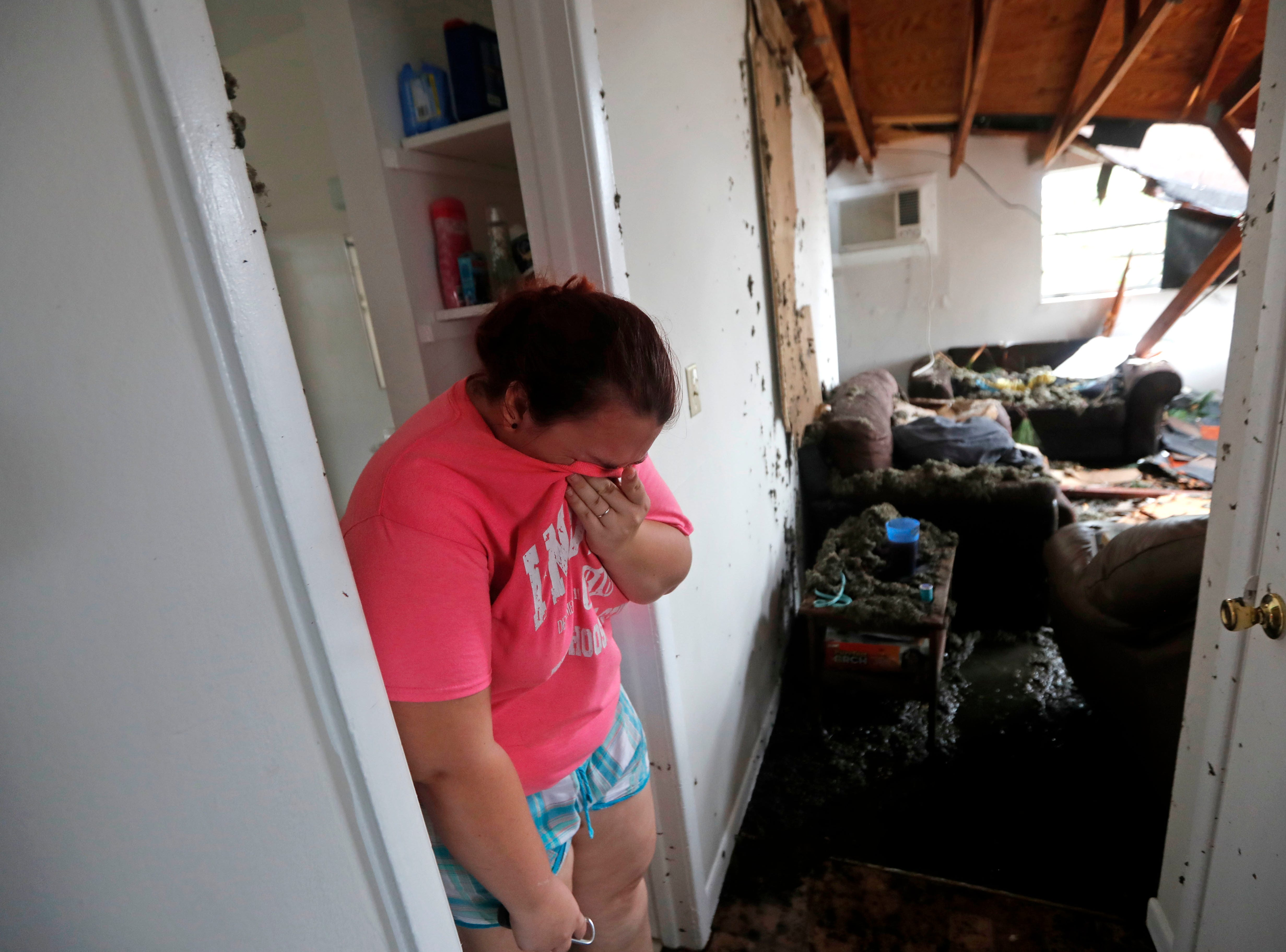 Kaylee O'Brian weeps inside her home after several trees fell on it during Hurricane Michael in Panama City, Fla., Wednesday, Oct. 10, 2018.