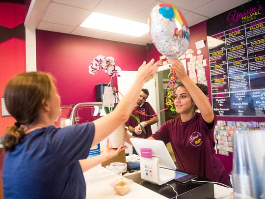 "Jessica Earl, left, surprises the staff at Yassin's Falafel House in downtown Knoxville with an orchid plant and a balloon Thursday after the restaurant was named ""Nicest Place in America."""