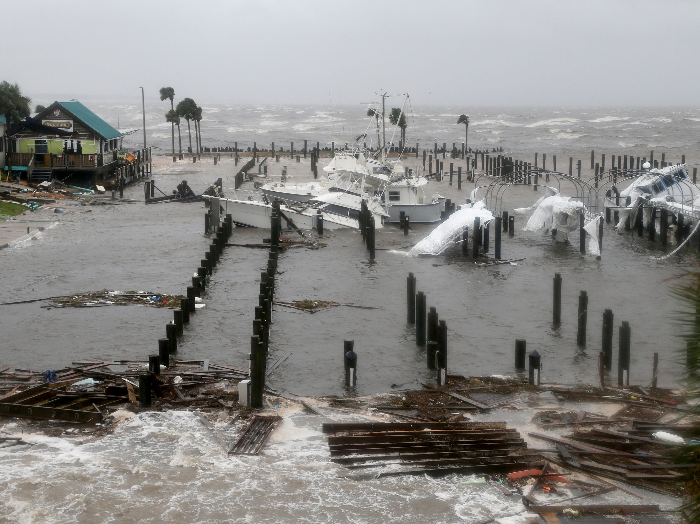 Storm Surge retreats from inland areas, foreground, where boats lay sunk and damaged at the Port St. Joe Marina, Wednesday, Oct. 10, 2018 in Port St. Joe, Fla. Supercharged by abnormally warm waters in the Gulf of Mexico, Hurricane Michael slammed into the Florida Panhandle with terrifying winds of 155 mph Wednesday, splintering homes and submerging neighborhoods.