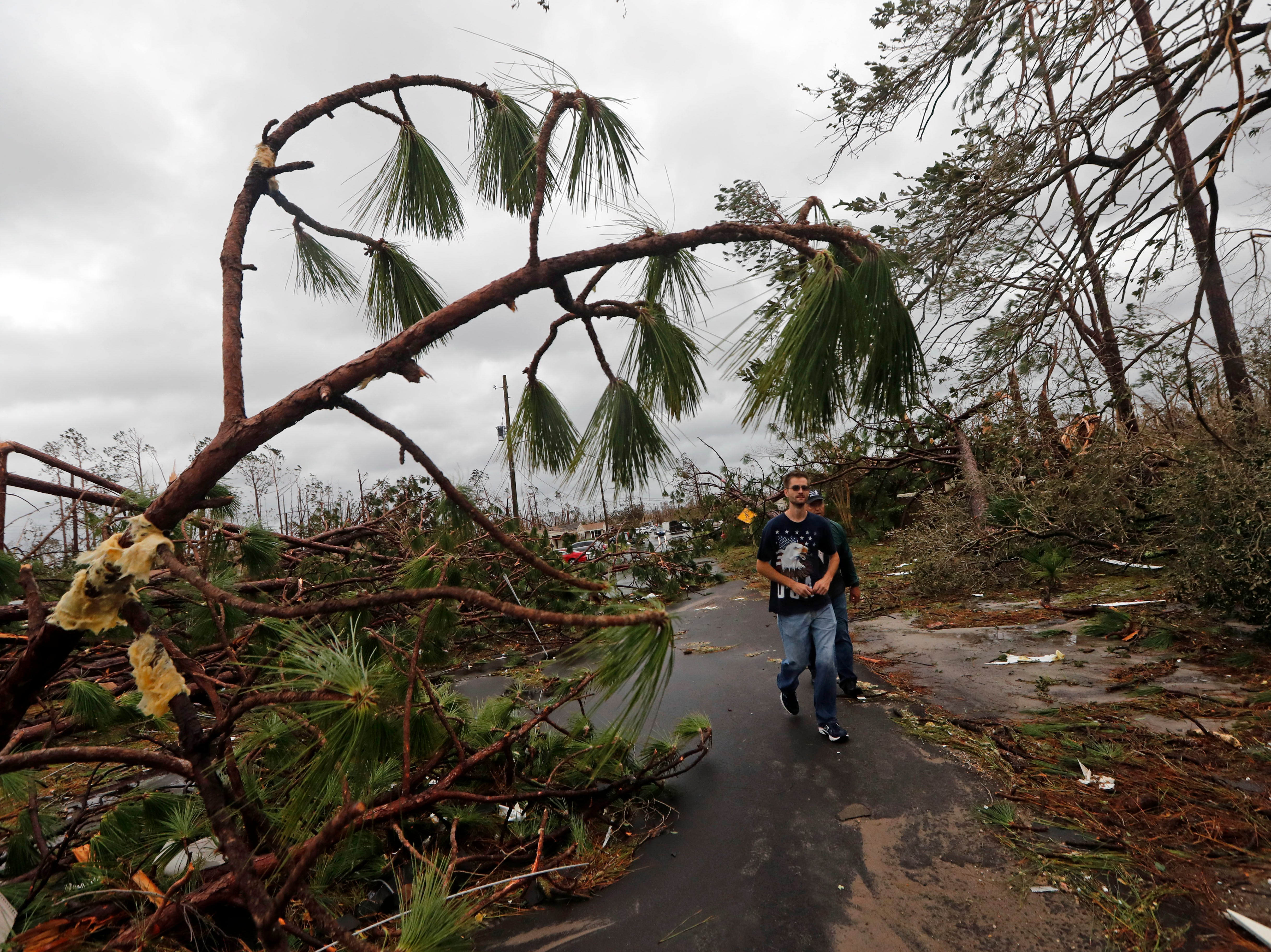 People walk through downed trees in a heavily damaged neighborhood in the aftermath of Hurricane Michael in Panama City, Fla., Wednesday, Oct. 10, 2018. Supercharged by abnormally warm waters in the Gulf of Mexico, Hurricane Michael slammed into the Florida Panhandle with terrifying winds of 155 mph Wednesday, splintering homes and submerging neighborhoods.