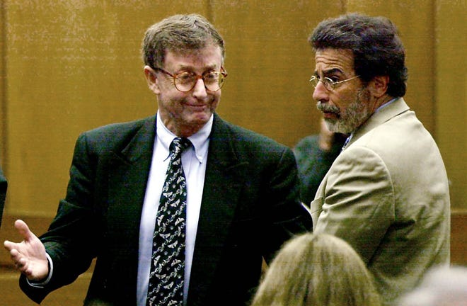 Michael Peterson, left, reacts after being found guilty of murdering his wife, in this Oct. 10, 2003, file photo, in a courtroom in Durham, N.C. At right is his attorney David Rudolf.