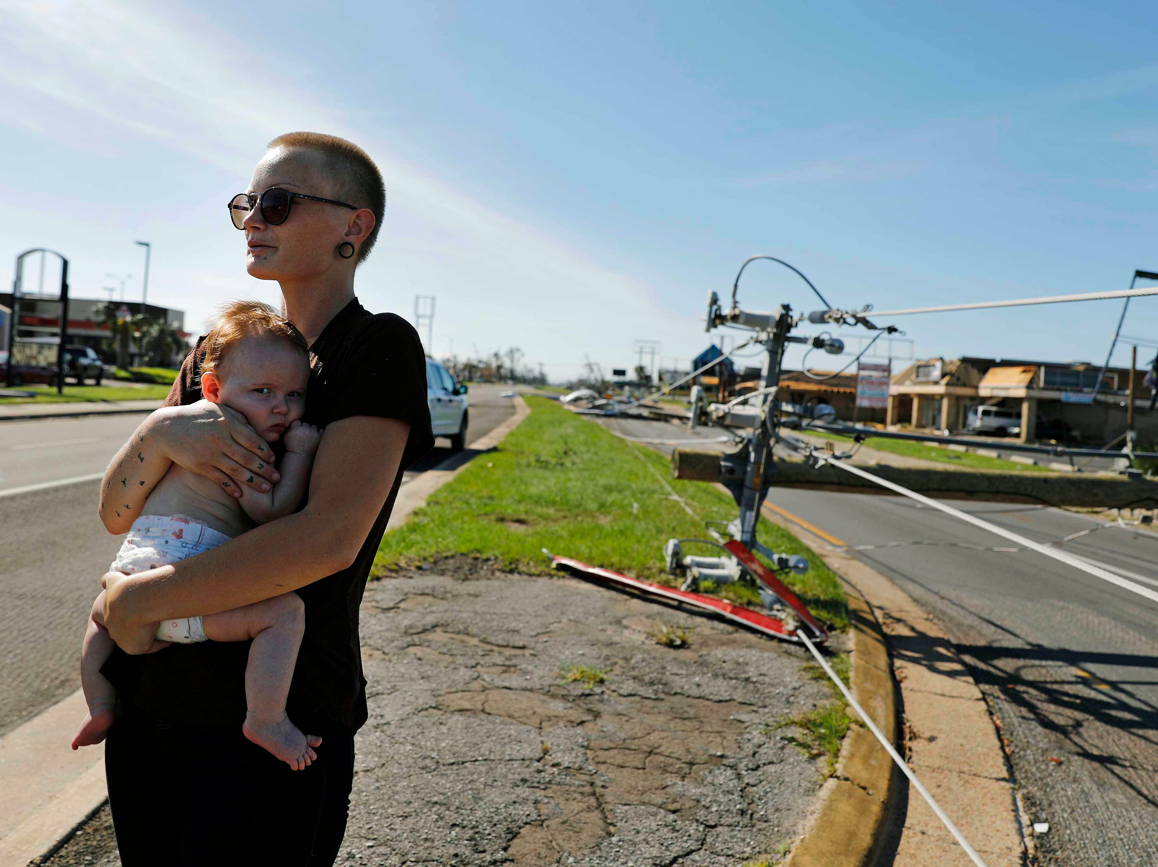 Kylie Strampe holds her four-month-old daughter, Lola, while surveying the damage from Hurricane Michael after riding out the storm in Callaway, Fla., Thursday, Oct. 11, 2018.