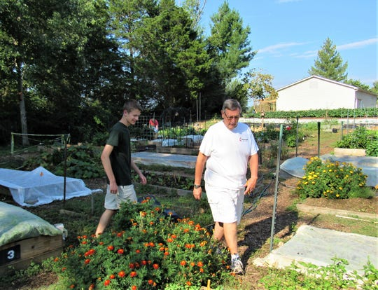 Michael Davis and Mike Smith look over zinnias in the community garden at CUMC. Certain flowering plants attract butterflies and honey bees to cross-pollinate.