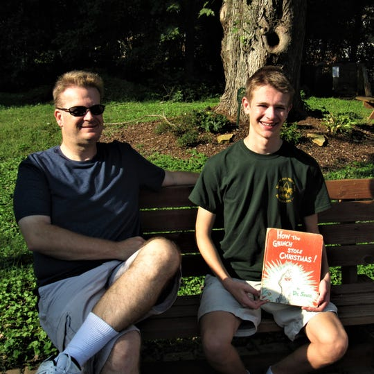 """Scott Davis and son Michael sit on a bench in a reading and meditation area.  Michael stocked the little library with a variety of books and this perennial favorite, """"How the Grinch Stole Christmas."""""""