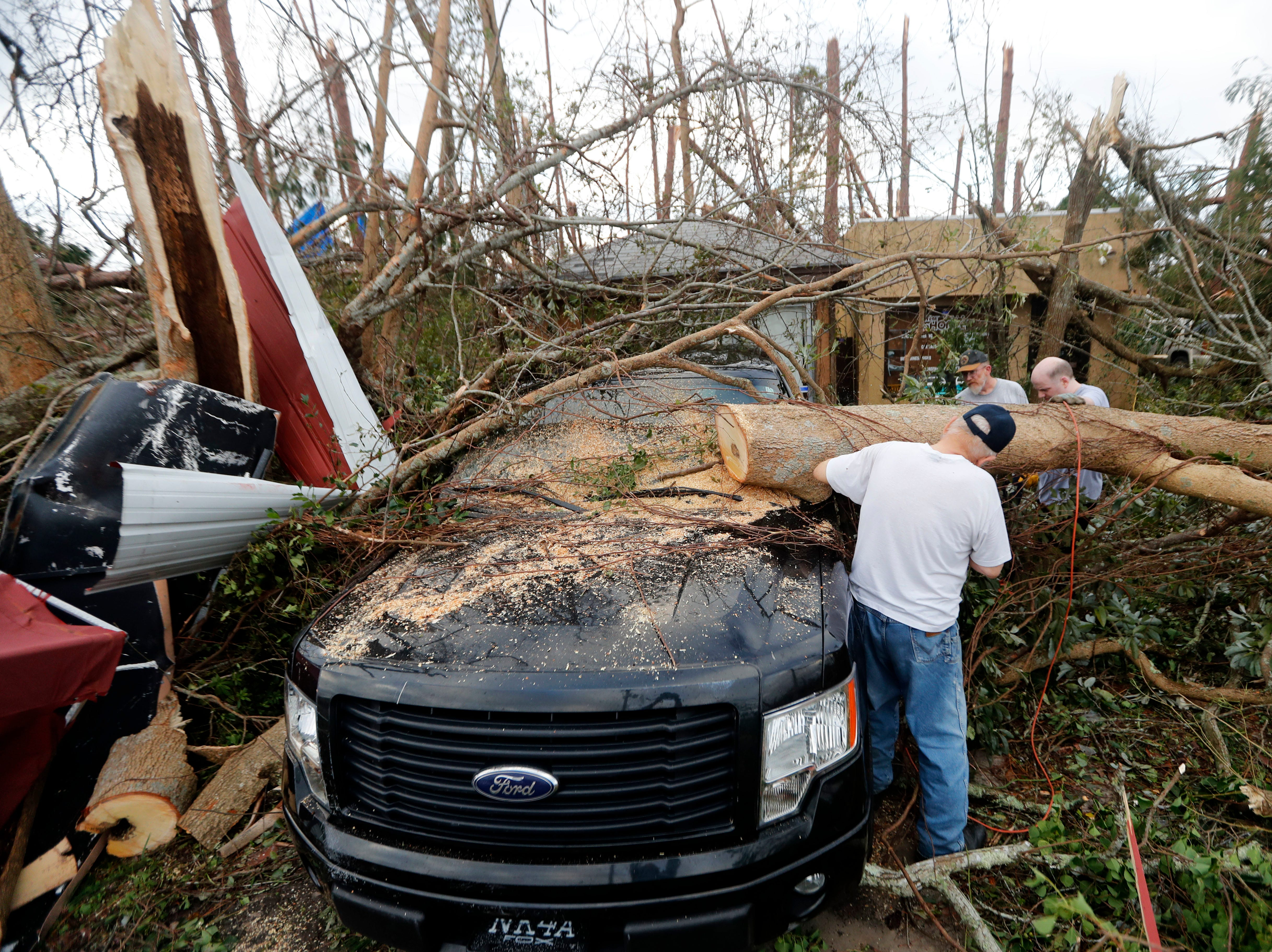 People cut away a tree that'll on a vehicle in the aftermath of Hurricane Michael in Panama City, Fla., Thursday, Oct. 11, 2018.