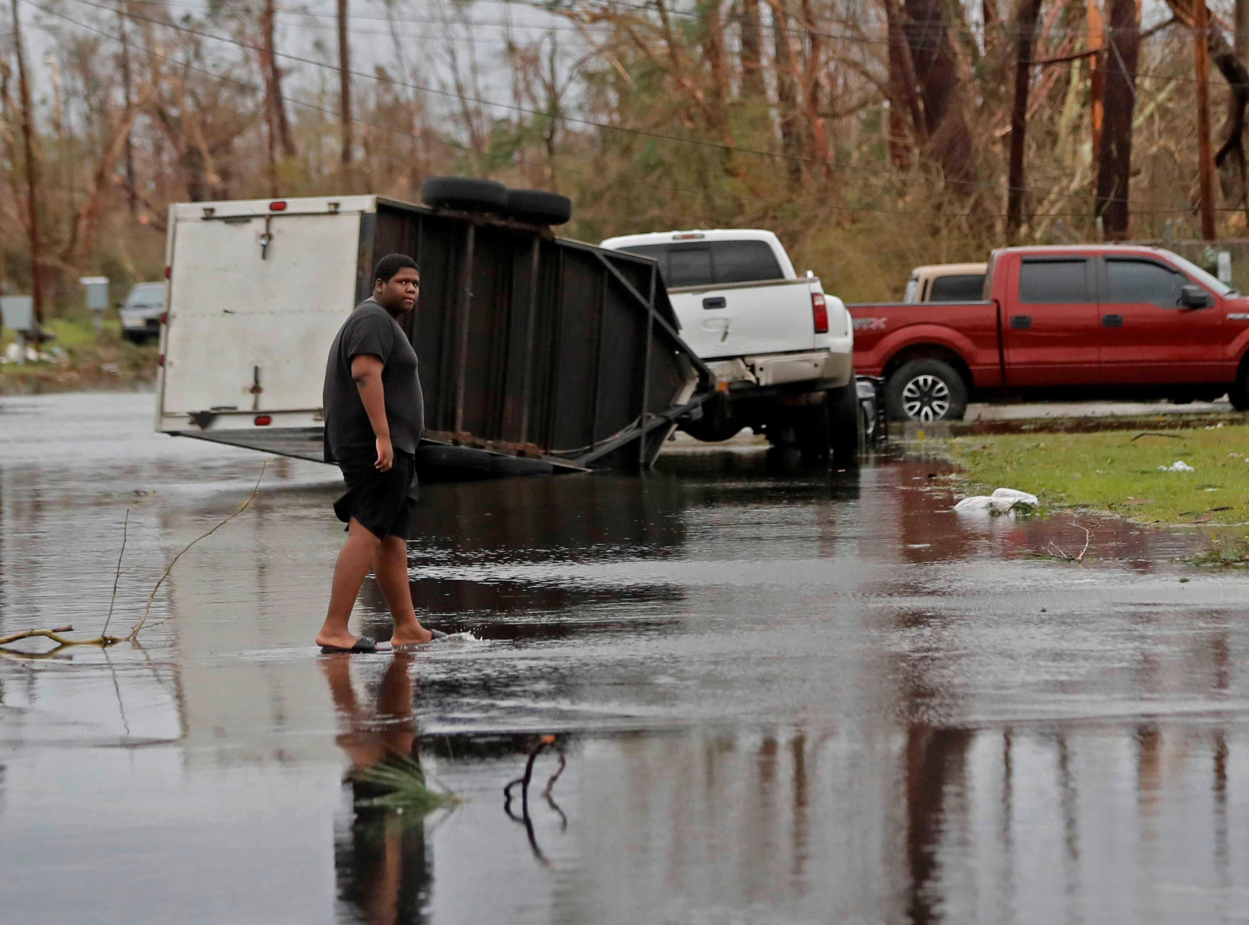 A man walks in the street of his heavily damaged neighborhood in the aftermath of Hurricane Michael in Panama City, Fla., Wednesday, Oct. 10, 2018. Supercharged by abnormally warm waters in the Gulf of Mexico, Hurricane Michael slammed into the Florida Panhandle with terrifying winds of 155 mph Wednesday, splintering homes and submerging neighborhoods.