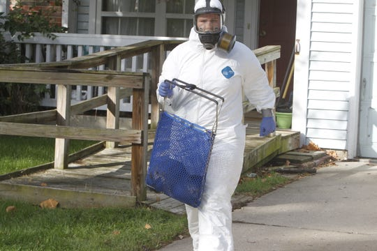 The first cat of an estimated 20 cats is removed from 3054 Portsmouth Drive West Thursday morning. The cat sliced open this animal control officer's protective suit in the back.