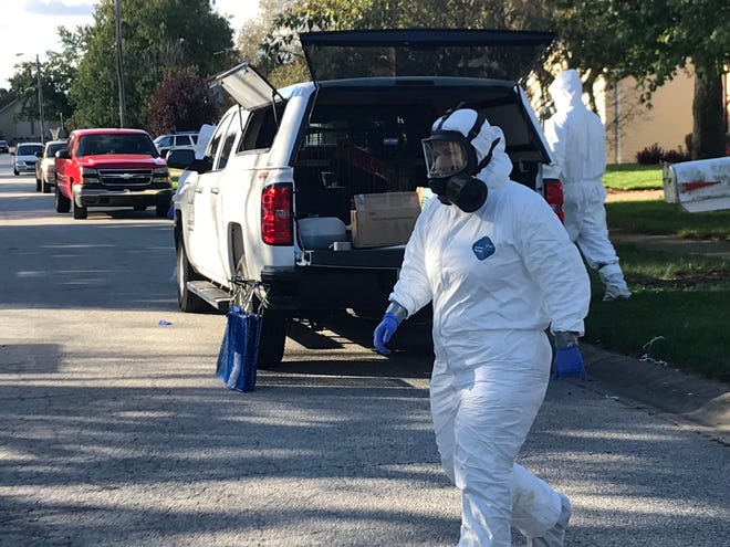 Animal Control officers dressed in protective suits and wearing respirators prepare to remove cats from 3054 Portsmouth Drive West while serving a search warrant Thursday morning.