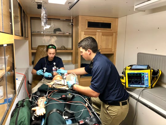 Paramedic student Macie Guillotte and EMS student Tyler Robichaux demonstrate life-saving skills in a simulation room made to look like an ambulance.