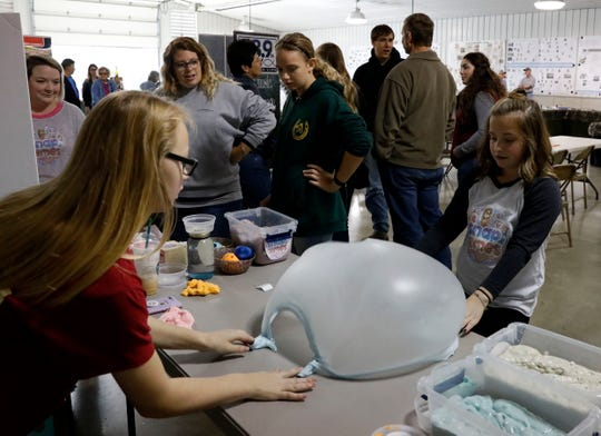 Madison DeMichael, right, and Madison Dabrielson, left, make a bubble with slime DeMichael made her for her business Snap Slimes Thursday, Oct. 11, 2018, at the Fairfield County Fair in Lancaster.