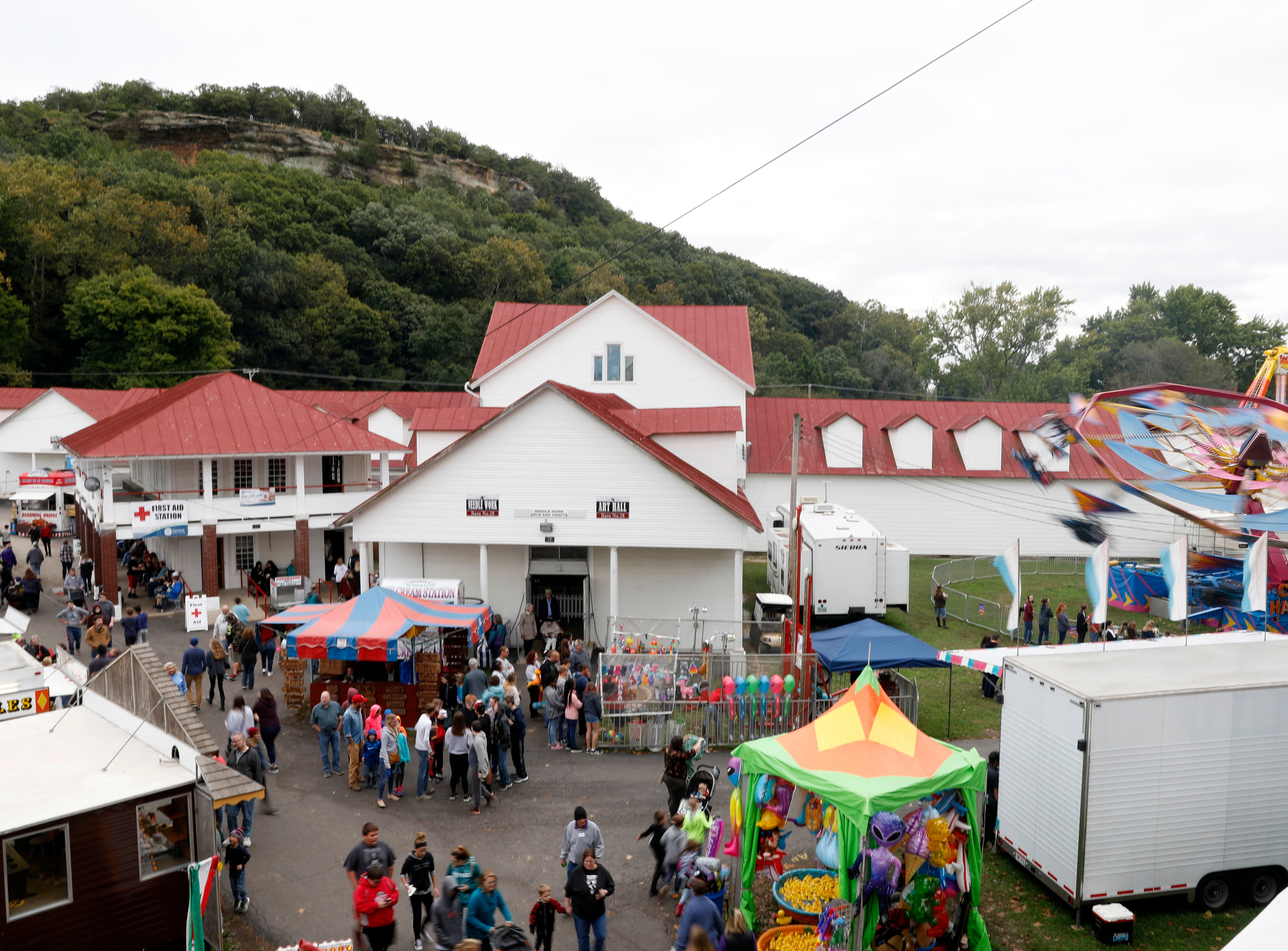 People mill through the midway near the art hall Thursday morning, Oct. 11, 2018, at the Fairfield County Fair in Lancaster.