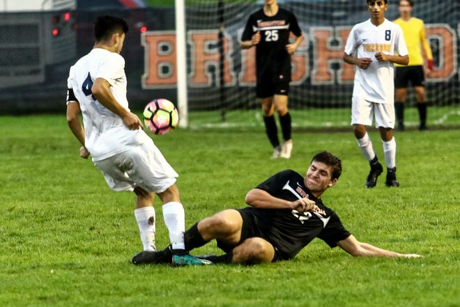 Brighton's Nolan Hoffman slides to stop Fordson's Hassan Jaber during the KLAA championship soccer game on Wednesday, Oct. 10, 2018.