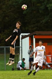 Brighton's Colin Adam skies for the header over Dearborn Fordson's Murad Othman during the KLAA championship soccer game on Wednesday, Oct. 10, 2018.