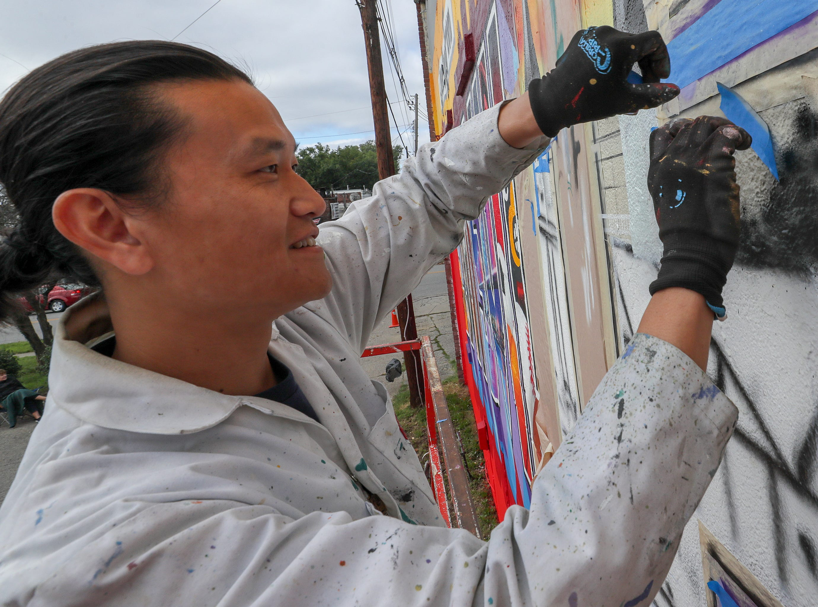 Artist Victor Ving puts the finishing touches on a mural on Central Avenue on Thursday morning.  The mural pays homage to post cards and is part of the Greetings Tour with photographer Lisa Beggs.  The pair have created 32 murals in 16 states with a goal of creating one in every state.  This is the first one in Kentucky.  The pair were in Alaska before coming to Louisville.  The building belongs to John and Mary Kay Dixon.  The group Often Seen Rarely Spoken also created some of the letters that depict the Louisville skyline, bourbon, Churchill Downs, Louisville Slugger, Louisville Cardinals and the Big Four Pedestrian Bridge.