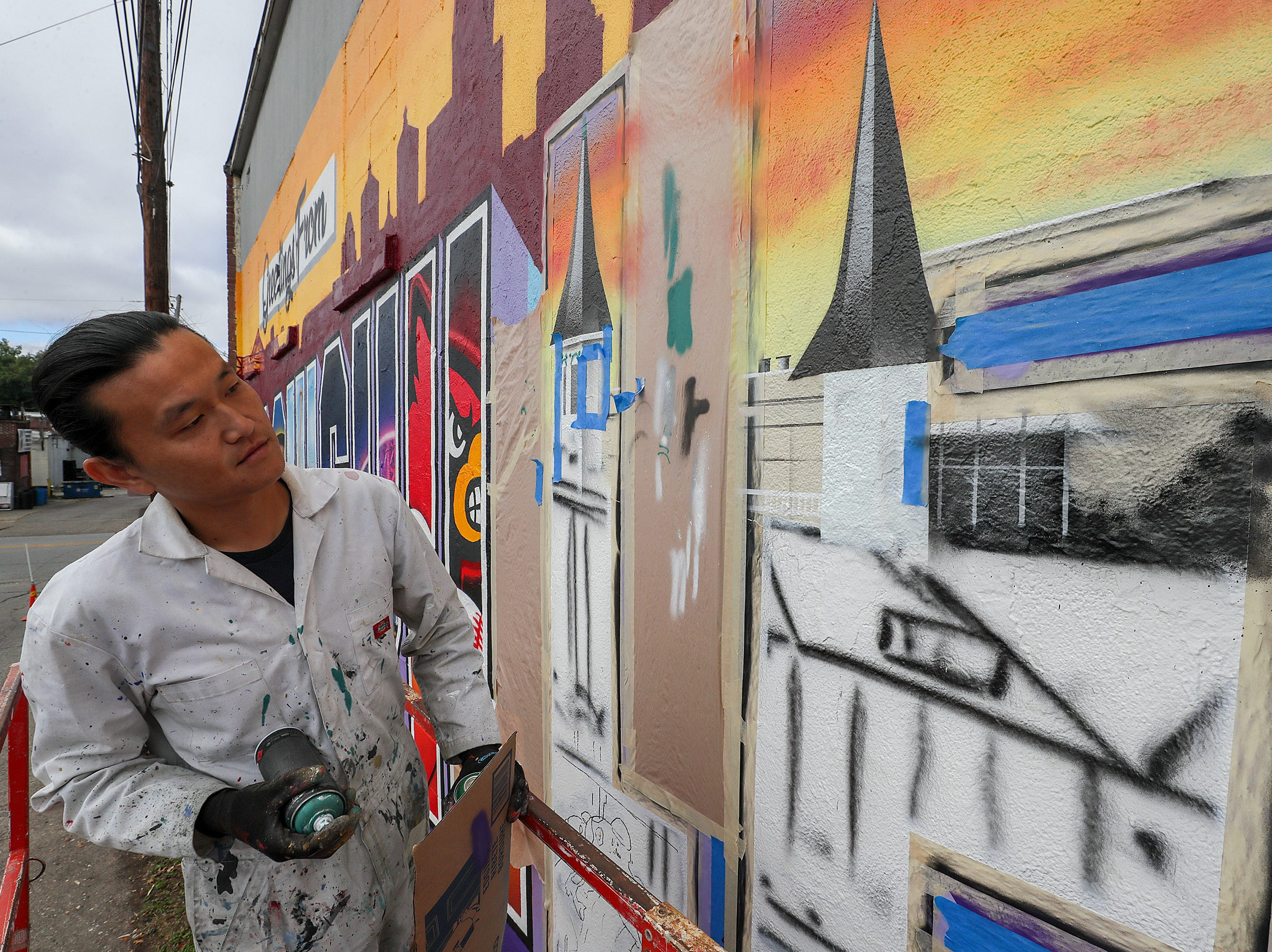 Artist Victor Ving regards his work as he puts the finishing touches on a mural on Central Avenue on Thursday morning.  The mural pays homage to post cards and is part of the Greetings Tour with photographer Lisa Beggs.  The pair have created 32 murals in 16 states with a goal of creating one in every state.  This is the first one in Kentucky.  The pair were in Alaska before coming to Louisville.  The building belongs to John and Mary Kay Dixon.  The group Often Seen Rarely Spoken also created some of the letters that depict the Louisville skyline, bourbon, Churchill Downs, Louisville Slugger, Louisville Cardinals and the Big Four Pedestrian Bridge.
