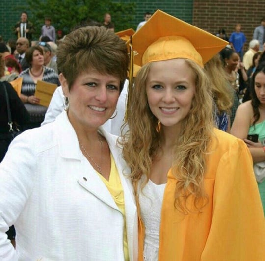 Erin Reyes at her Holt High School graduation in 2013, with her late mother, Lisa Self. Self, 45, took her own life shortly after graduation and Reyes has pursued art to deal with her grief.