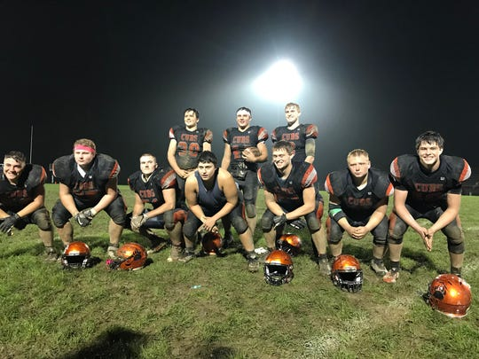 Lucas' Jeb Grover (back, middle) poses with his offensive linemen and blocking backs after setting the career-rushing record at Lucas High School last week.