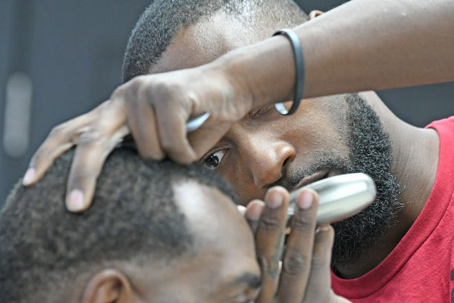 Damien Beauford cuts the hair of R.D. DeLoach Jr. on Thursday at Barberz Inc. Barber Studio on Park Avenue West.