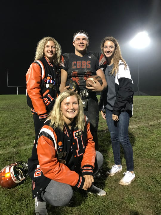 Jeb Grover poses with his sisters after setting the career-rushing record at Lucas High School last week.