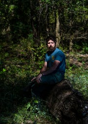 "A contestant on this season of NBC's ""The Voice,"" Keith Paluso, a Germantown park ranger, sit on a log in Wolf Park Nature Park Thursday October 11, 2018."