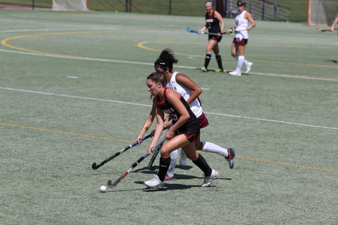 Rhodes College field hockey player Hailey Mules escapes pressure from a defender.
