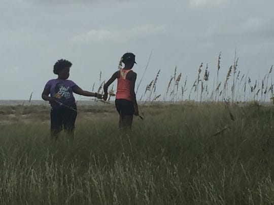 Latrice Hawkins (left) and Chinita Muhammad gather sea oats on Deer Island for an art project on their Carpenter Art Garden field trip.