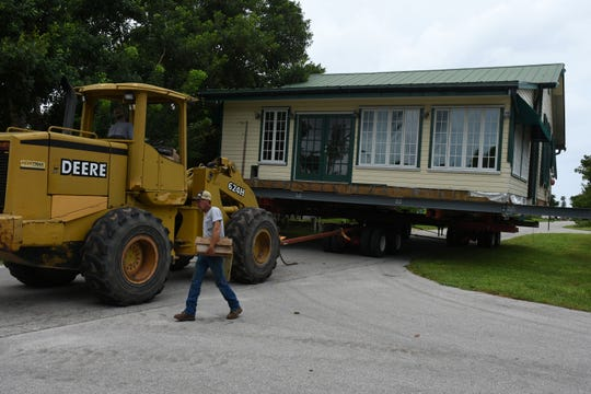 The house moves Ð slowly Ð down Pear Tree Avenue. A home originally built from cypress planks salvaged from a 1910 shipwreck was moved Monday from one location in Goodland to another off the water.