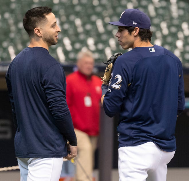 Outfielders Ryan Braun and Christian Yelich chat during a workout a day before the start of the NLCS.