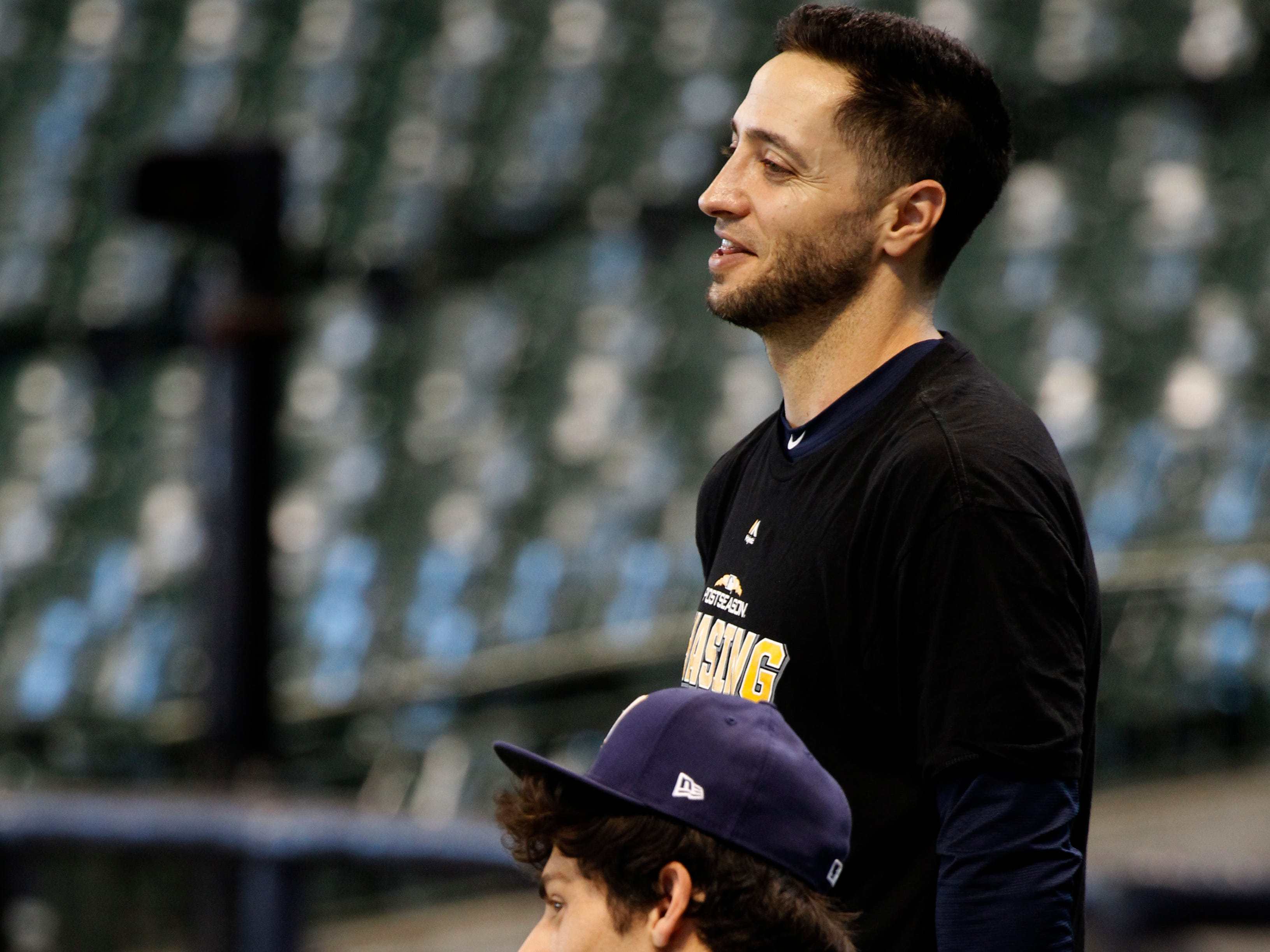 Ryan Braun (standing) and Christian Yelich wait their turn during batting practice on Wednesday at Miller Park.