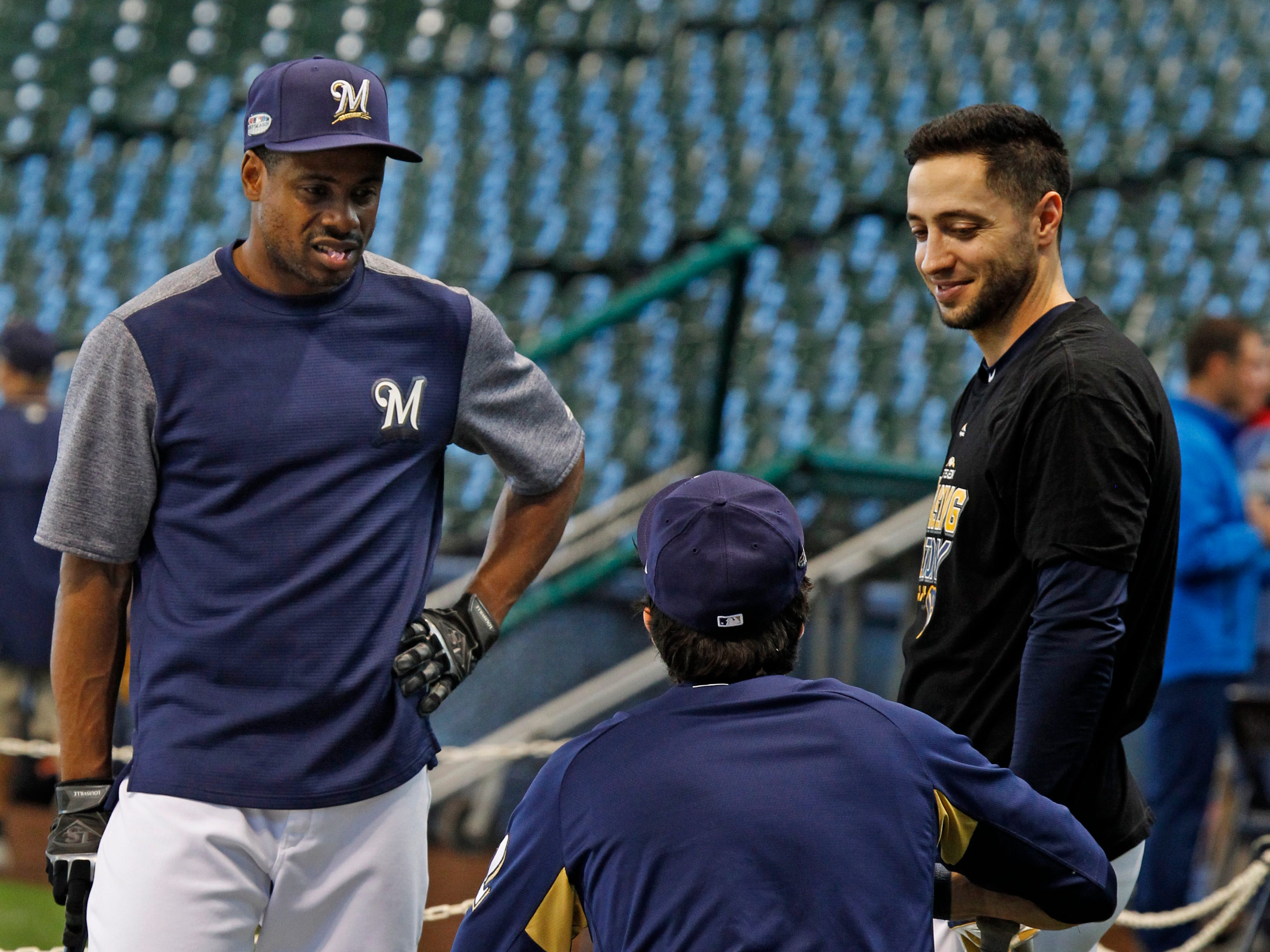 Brewers outfielders Curtis Granderson (left), Ryan Braun (right) and Christian Yelich chat during practice Wednesday, at Miller Park.