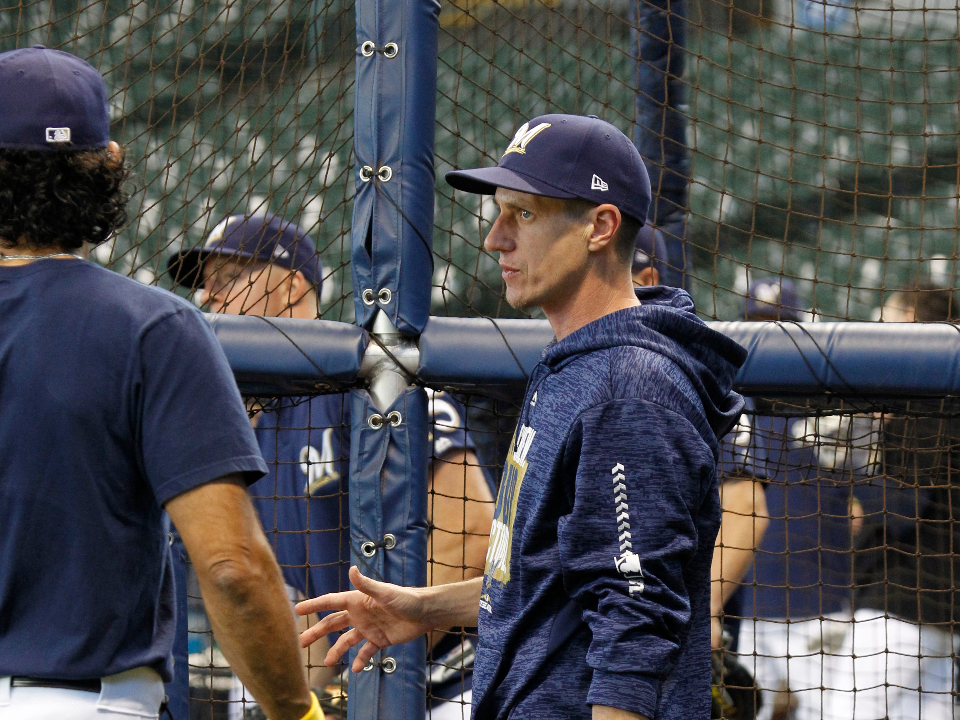 Brewers manager Craig Counsell talks with first base coach Carlos Subero during practice Wednesday at Miller Park.