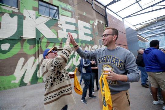 Brewers fans Tony Wilson (left) and Alex Uebelacker, both of Milwaukee, high five as they watch the Brewers' playoff game Sunday afternoon at the beer garden outside Fiserv Forum. The game was broadcast on the MLB Network, which many fans did not get on their home TVs.